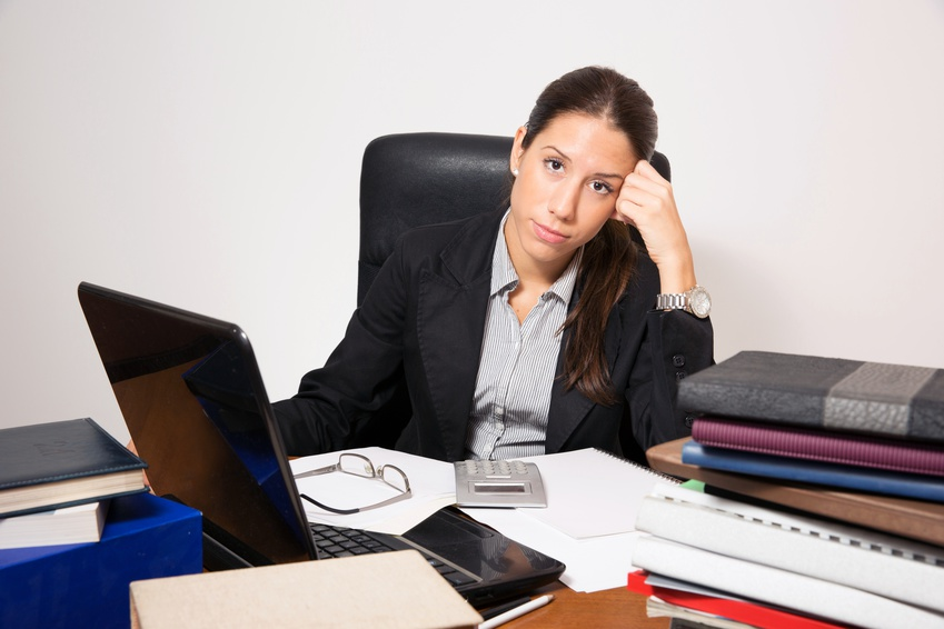 Young business dressed woman working at office desk.